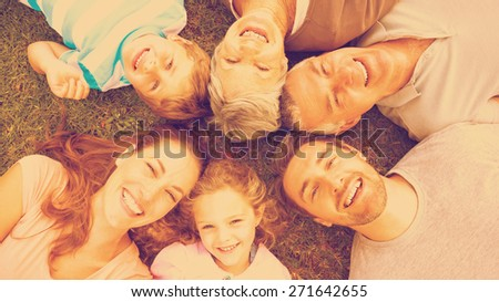 High angle portrait of an extended family lying in circle at the park - stock photo