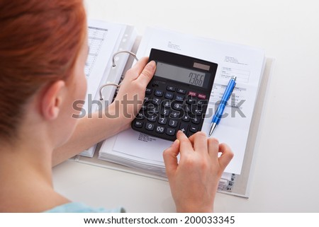 High angle portrait of beautiful young woman calculating invoice at desk - stock photo