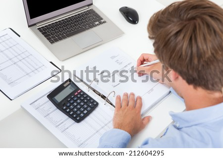High angle portrait of businessman calculating tax at desk in office - stock photo