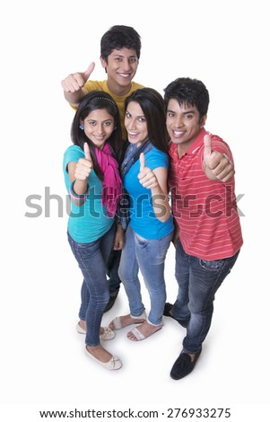 High angle portrait of college students gesturing thumbs up against white background - stock photo