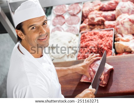 High angle portrait of confident butcher cutting meat at counter in butchery - stock photo