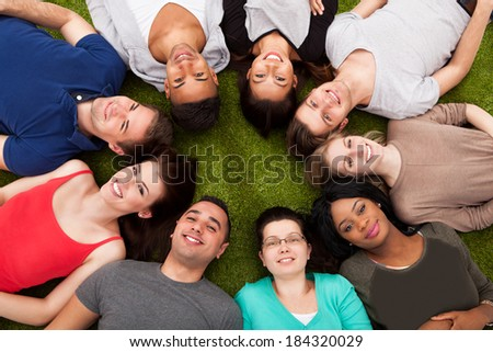 High angle portrait of confident college students lying on grass at campus