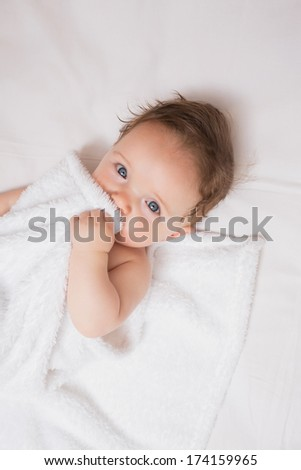 High angle portrait of cute baby boy holding blanket in crib - stock photo