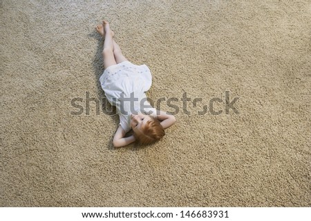 High angle portrait of little girl lying on carpet at home - stock photo