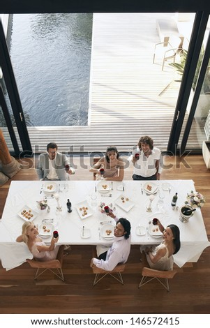 High angle portrait of multiethnic friends toasting wine at dinner party - stock photo