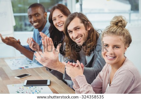 High angle portrait of smiling business people clapping at desk in office