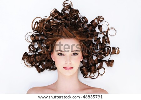 high angle portrait of the pretty young woman with beauty curly hairs -lyin? on the floor - stock photo