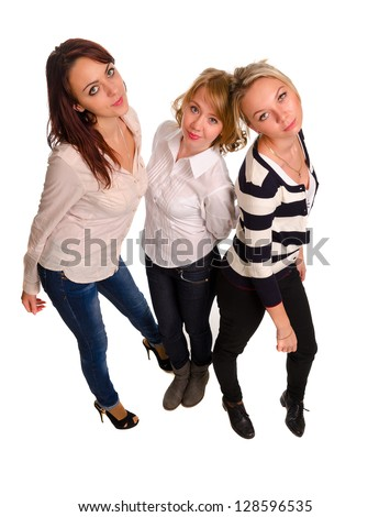 High angle portrait of three attractive trendy fashionable female friends standing in a close group looking up at the camera isolated on white - stock photo