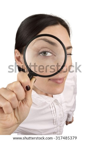 high angle portrait of young woman wearing white shirt looking in magnifying glass. Studio shot isolated over white