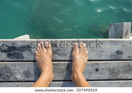 High angle POV of man's bare feet standing at edge of wooden dock sprinkled with fine white sand above aqua green sea water in natural morning light - stock photo