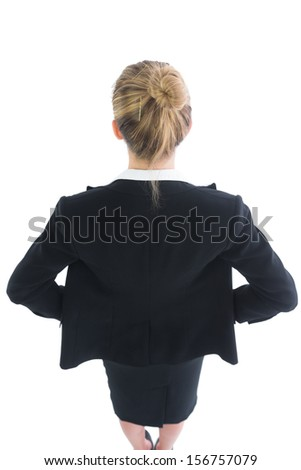 High angle rear view of blonde young businesswoman posing with hands on hips