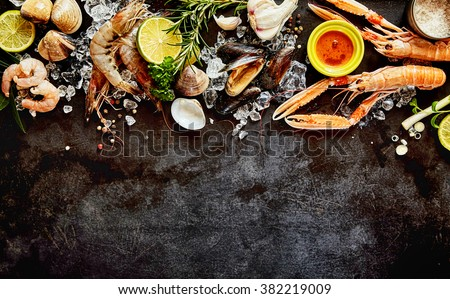 High Angle Seafood Cuisine Background Image with Fresh Shellfish - Shrimp, Langostino, Mussels and Clams - and Ingredients on Dark Background with Copy Space - stock photo
