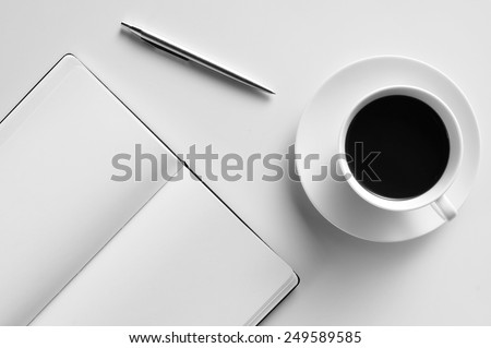 high-angle shot of a blank notepad, a pen and a cup of coffee on a white table - stock photo