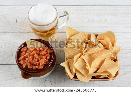 High angle shot of a bowl of corn chips a crock full of fresh salsa and mug of beer on a whitewashed rustic wood table. Horizontal format.  - stock photo