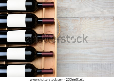 High angle shot of a case of red wine bottles with blank labels  on a rustic white wood table with copy space. Horizontal format. - stock photo