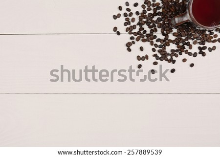 High angle shot of a coffee mug and fresh roasted beans in the corner of the frame on a white wood table. Horizontal format with copy space. - stock photo