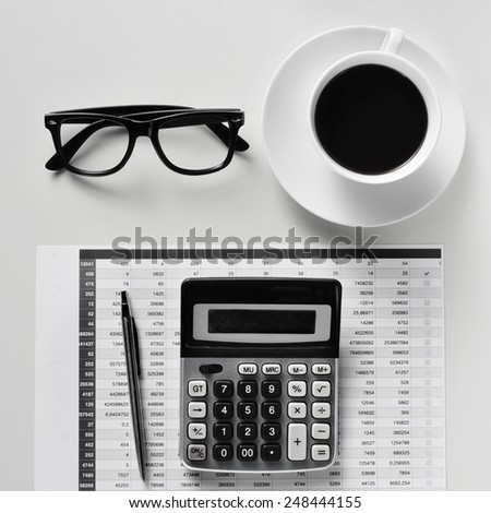 high-angle shot of a desk with a calculator, a pen, a balance sheet, eyeglasses and a cup of coffee in an office - stock photo