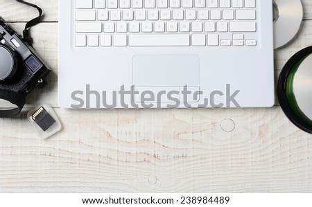 High angle shot of a digital photography workspace. The closeup includes a computer keyboard, CD's, memory card, and digital camera. Horizontal format with copy space, on a white rustic table. - stock photo