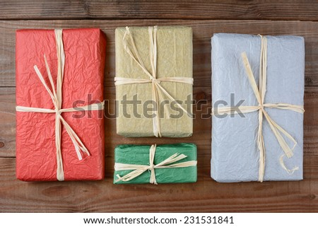 High angle shot of a four presents wrapped with colorful tissue paper. The gifts are tied with raffia and are laying on a rustic wood table. Horizontal format. - stock photo