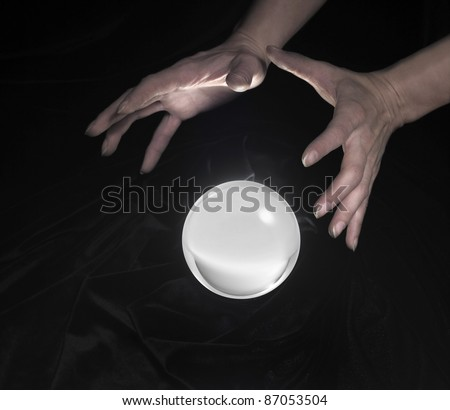 high angle shot of a glowing crystal ball surrounded by black crinkly fabrics and two hands around - stock photo