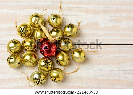 High angle shot of a group of Christmas jingle bells on a white wood table. Horizontal format  with one red bell surrounded by a lot of smaller gold bells. - stock photo