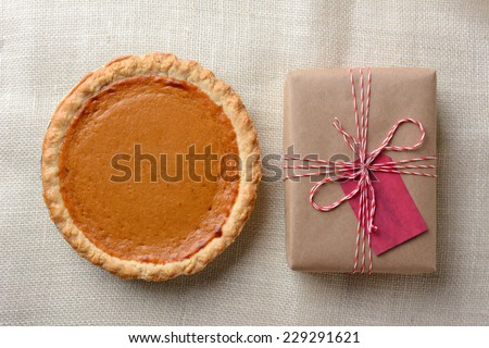 High angle shot of a holiday pumpkin pie and plain paper wrapped present. The brown gift is tied with red and white string and has a red gift tag. Horizontal format. - stock photo