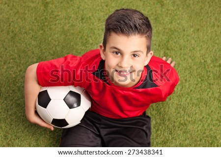 High angle shot of a junior football player in a red jersey sitting on grass holding a ball and smiling - stock photo