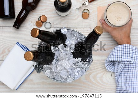 High angle shot of a man holding a glass of beer with a metal bucket with unopened bottles. The rustic wood table has empty bottles and caps and an bottle opener.  - stock photo