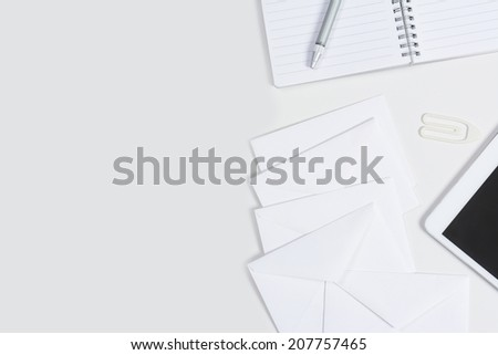 High angle shot of a neat white desk with copy space. White office objects set to the right side. Items include, note pad, tablet, computer, pen, envelopes and a paper clip. - stock photo