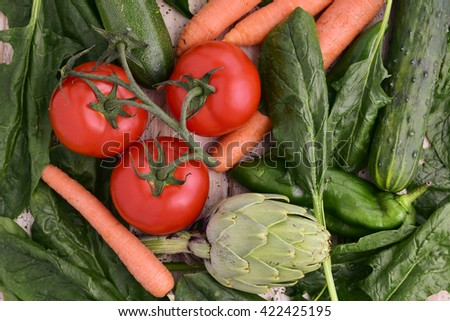 high-angle shot of a pile of different raw vegetables, such as spinach, artichokes, cucumbers, zucchinis, green peppers, tomatoes and carrots - stock photo