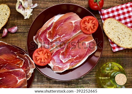 high-angle shot of a plate with spanish pan con tomate y jamon, sliced bread topped with tomato and serrano ham and dressed with olive oil, on a rustic wooden table - stock photo
