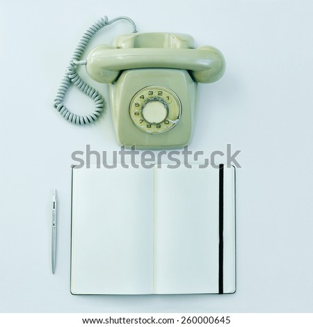 high-angle shot of a rotary telephone, a pen and a blank notepad on a table - stock photo