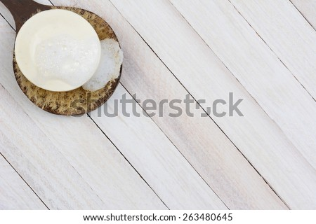 High angle shot of a sudsy bar of soap on a scrub brush. On a rustic wood surface the brush and soap are in the upper left corner of the frame leaving room for your copy. - stock photo
