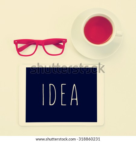 high-angle shot of a table with a pair of red plastic-rimmed eyeglasses, a cup of tea and a tablet computer with the word idea in its screen - stock photo