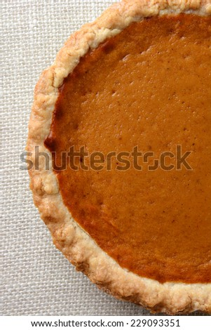 High angle shot of a Thanksgiving Pumpkin Pie.  Pumpkin pie is a traditional desert served on the American Holiday. Vertical format, only half the fie filling the frame. - stock photo