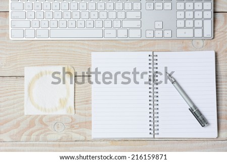 High angle shot of a white rustic desk with a modern keyboard, notebook and napkin with a coffee stain. Horizontal format. - stock photo