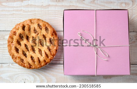 High angle shot of an apple pie and a pink bakery box. Horizontal format on a rustic white wood kitchen table.  - stock photo