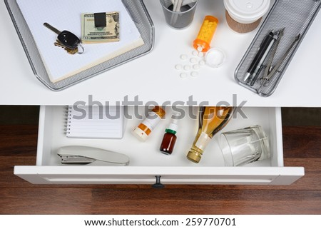 High angle shot of an open desk drawer showing the items inside. The top of the desk has a coffee cup, spilled prescription bottle, in-box, car keys and money clip. - stock photo