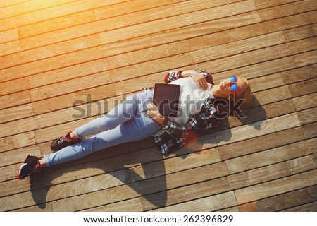 High angle shot of carefree young woman in summer glasses lying on the wooden jetty in the sun,young freelancer woman resting after work with digital tablet outdoors, enjoy her holiday or break, flare - stock photo