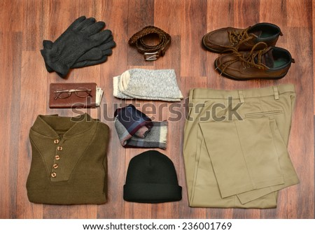 High angle shot of men's winter clothes laid out on a dark wood floor. Items include, Sweater, Scarf, Gloves, wool Socks, Pants, Boots, belt, Knit Cap, Wallet, and Glasses. Horizontal Format. - stock photo