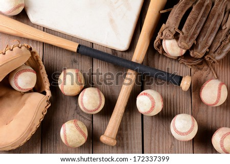 High angle shot of old and use baseball equipment on a rustic wood surface. Items include, baseballs, bats, home plate, catchers mitt and glove. - stock photo