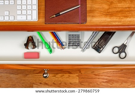 High angle shot of open desk drawer with work items inside. Red oak desktop has computer keyboard, executive notepad and pen. Wooden oak floor underneath desk.  - stock photo