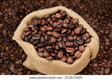High angle shot of roasted coffee beans in a burlap sack. the bag is sitting on a  table full of beans that are out of focus. Horizontal format.