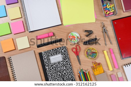 High angle shot of school supplies laid out on a wood desk. Back to School concept with paper, pads, pencils, notebooks, scissors, erasers and more. Horizontal format at an angle. - stock photo