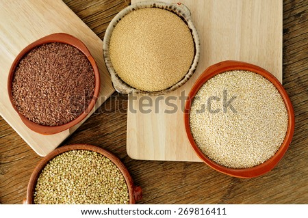 high-angle shot of some earthenware bowls with amaranth, quinoa, brown flax and buckwheat seeds on a rustic wooden table - stock photo
