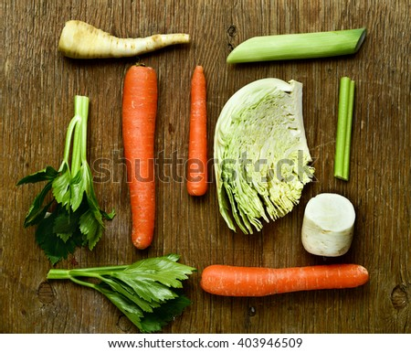 high-angle shot of some pieces of different raw vegetables, such as carrots, parsnips, turnips, cabbage and celery, on a rustic wooden table - stock photo