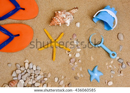 high-angle shot of some summer stuff, such a pair of flip-flops, a conch, a starfish, some pebbles and seashells or a small beach pail and a toy shovel, on the sand of a beach - stock photo