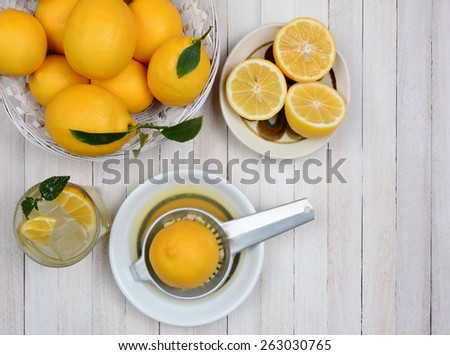 High angle shot of squeezing lemons still life shot from a high angle on a rustic white wood kitchen table. - stock photo