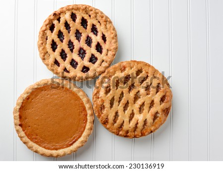 High angle shot of three pies, apple, pumpkin, and cherry. Horizontal format on a white beadboard surface. The pies are favorites for the  American Holidays, Thanksgiving and Christmas. - stock photo