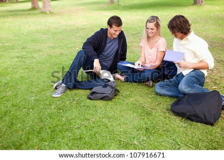 High angle-shot of three students in a park studying - stock photo